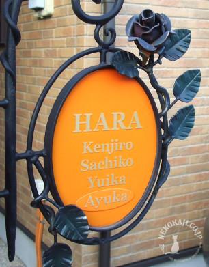 バラのアイアンブラケットとオレンジ色の 真鍮サイン